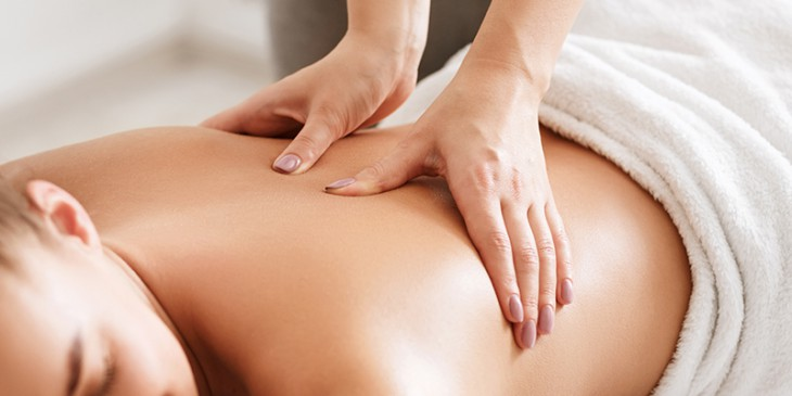 Body care. Young girl having massage, relaxing in spa salon, closeup